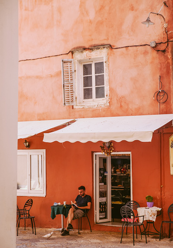 21st July 2019,Corfu,Greece:  A local man reading book in a cafeteria in Corfu. the traditional buildings of Corfu and cafeterias can be seen in the background. Corfu old town is famous for its Venetian colorful buildings and narrow streets.