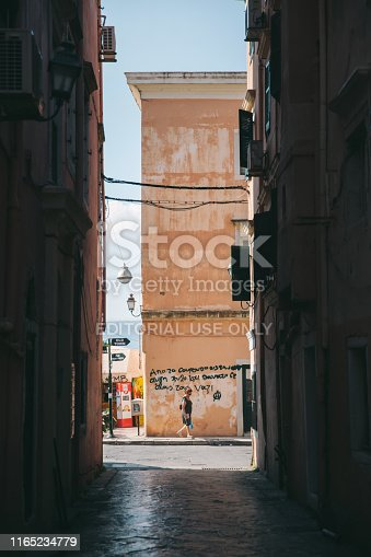 21st July 2019,Corfu,Greece:  One senior lady walking at a narrow street in Corfu. the traditional buildings of Corfu and cafeterias can be seen in the background. Corfu old town is famous for its Venetian colorful buildings and narrow streets.