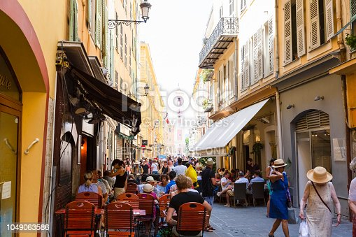 Nice, France July 24, 2018: Nice, street in old town full of shops, restaurants and coffee places where tourist and local enjoying day shopping, having meal and coffee