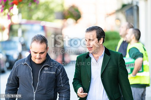 istock Street in Pimlico Chelsea or Belgravia area with two men pedestrians business friends walking on pavement talking closeup 1125781829