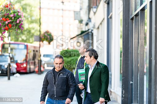 istock Street in Pimlico Chelsea or Belgravia area with two men pedestrians business friends walking on pavement talking during day 1125782820