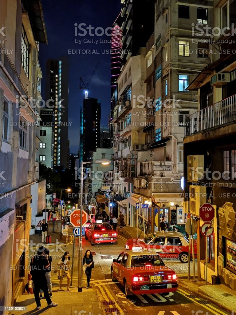 Street in Soho by night, Hong Kong Island People at night  walking on a street in Soho, a lively nightlife area located in Central and bordering between Lan Kwai Fong and Sheung Wan. Hong Kong island Architecture Stock Photo