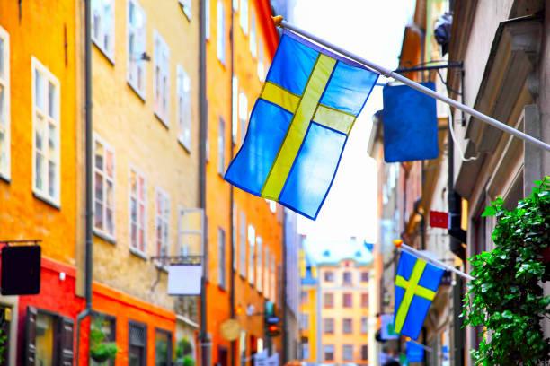 street in stockholm with swedish flags - szwecja zdjęcia i obrazy z banku zdjęć