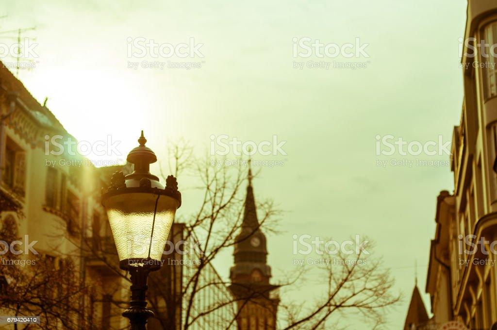 Lampe de rue contre la construction d'architecture et un ciel nuageux et soleil. Subotica, Serbie. photo libre de droits