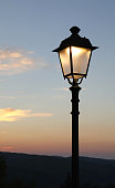 A street lamp comes on at dusk
