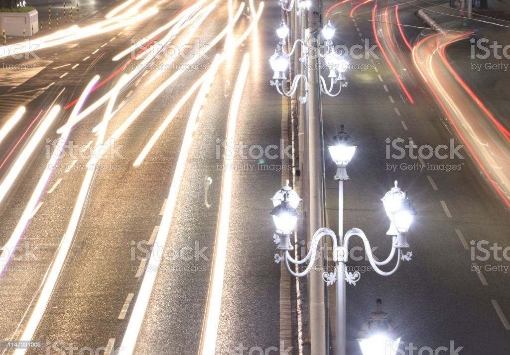 Street lamp in the night with abstract of movement car light on the...