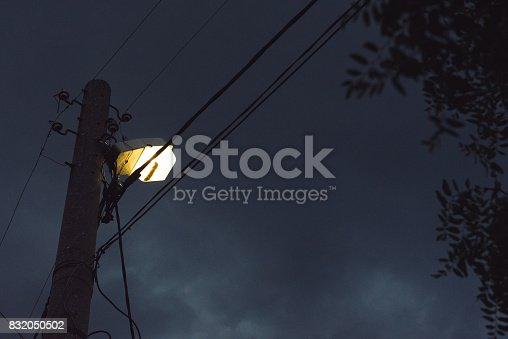A lone lamp in a far desolate place is attached to an electricity cabling pole - as seen from below on a dark cloudy sky background