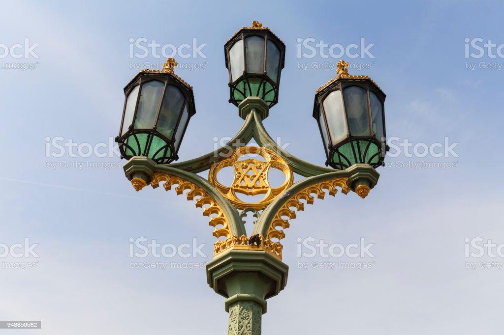 Street lamp on Westminster Bridge on the background of blue sky, London, United Kingdom. stock photo