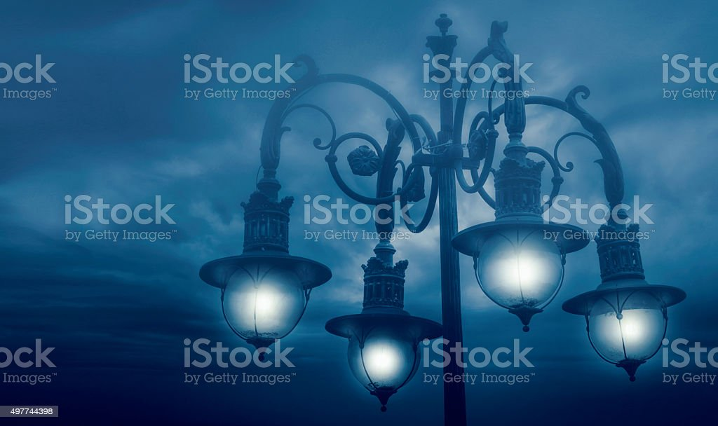 street lamp shining at night against cloudy sky stock photo