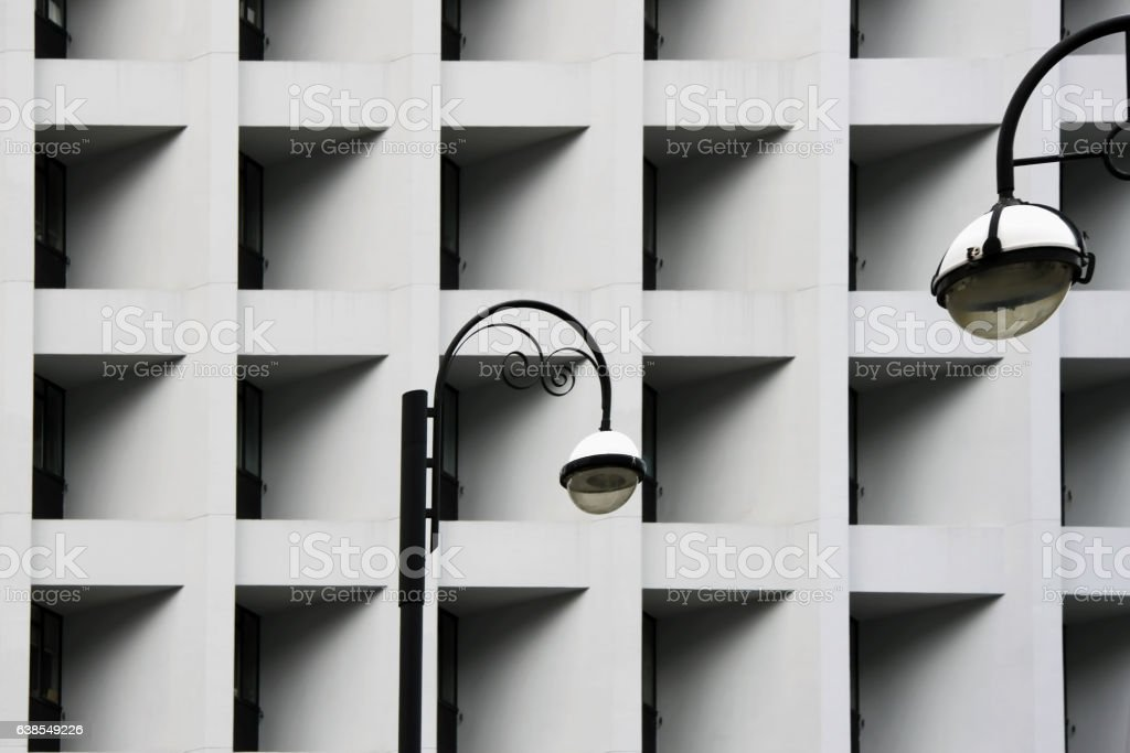 Street lamps against Modern abstract urban building. Detailed geometric black stock photo