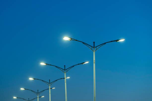 street lamps under blue sky at dusk