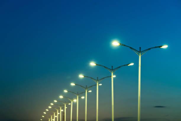 lampadaires sous un ciel bleu au crépuscule - éclairage public photos et images de collection