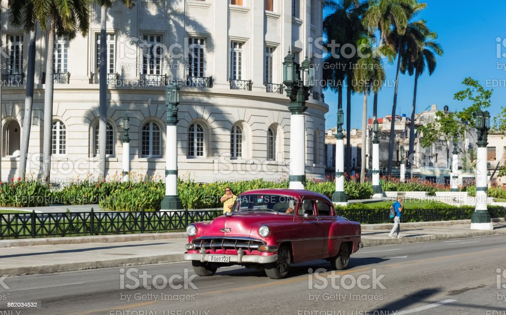 Street life view with cuban peoples on the street and american a brown red  Chevrolet vintage car drive before the Capitolio on the main street in Havana City Cuba - Serie Cuba Reportage stock photo