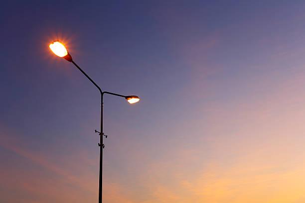 Street light illuminated sunset stock photo