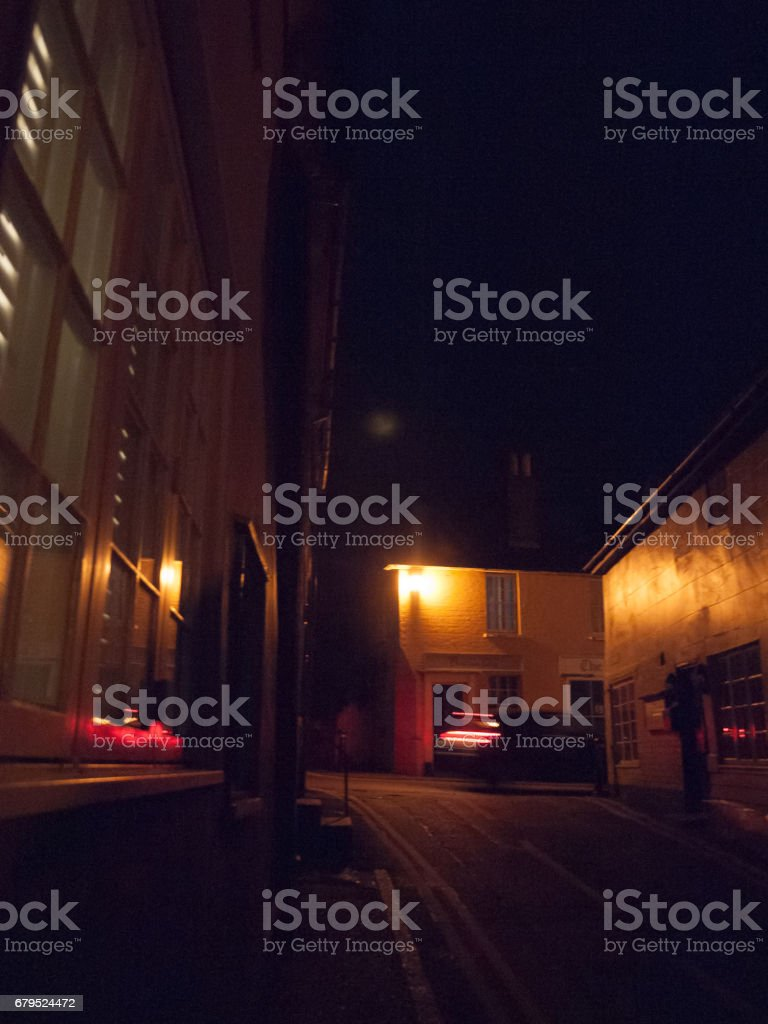 street light outside in the dark at night with a car moving blurred royalty-free stock photo