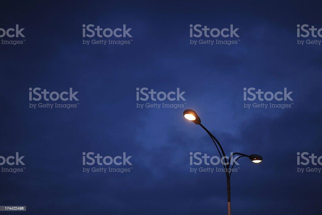 Street light against evening blue sky background.