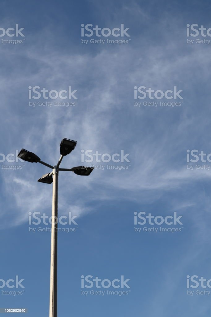Street light pole with four lamps, blue sky background.