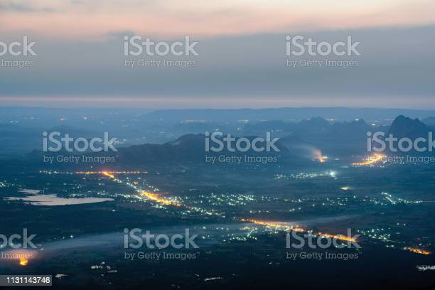 Photo of Street lights and small town at dawn with mountain range