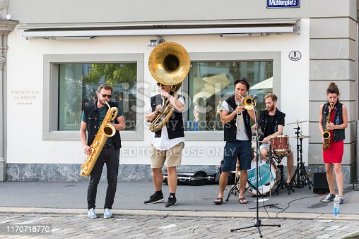 Lucerne, Switzerland - August 21, 2018: The bare brass band busking at Lucerne, Switzerland. Young boys and girls are earning money by using classic musical instruments (trombone, saxophone, oboe, drums, guitar, and soloist) in street of Geneva. They are street musicians.