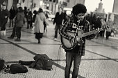 Lisbon, Portugal - January 2, 2015: A street musician plays a guitar in the Rua Augusta street in Lisbon downtown.