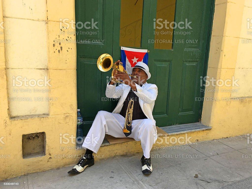 Street musician Havana, Cuba - April 27, 2016: Elegant black trumpeter with Cuban flag behind him playing on the street at the city center of Havana, Cuba. Adult Stock Photo