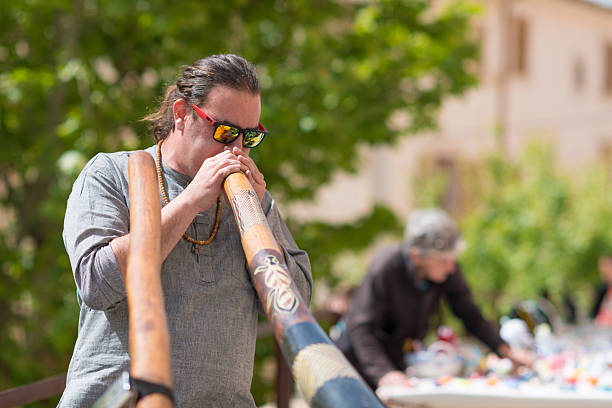 street musician playing didgeridoo at city market day sineu mallorca - didgeridoo stock photos and pictures