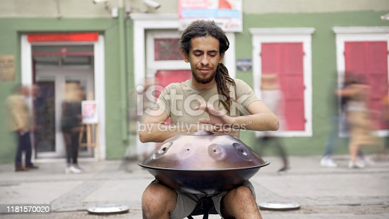 Street musician playing handpan.