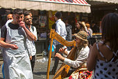 Jerusalem, Israel: May 10, 2019: Street musician playing music, harpist playing a harp on the Mahane Yehuda, famous market of Jerusalem Old City, Jerusalem