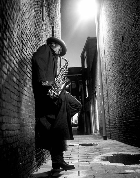 straßenmusiker spielen saxophon in alley - altsaxophon stock-fotos und bilder