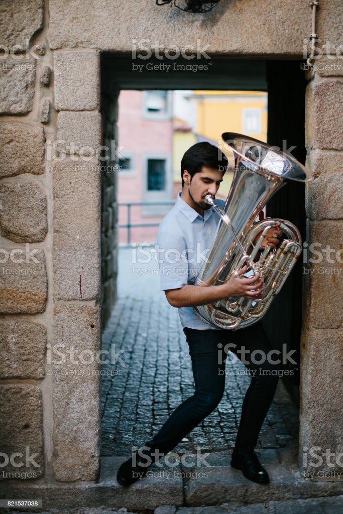 Street musician playing tuba outdoor in European city stock photo