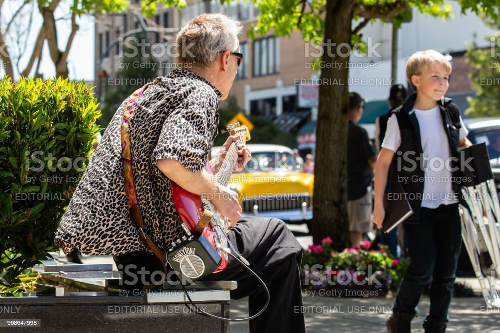 Street musician plays guitar as a boy passes by stock photo