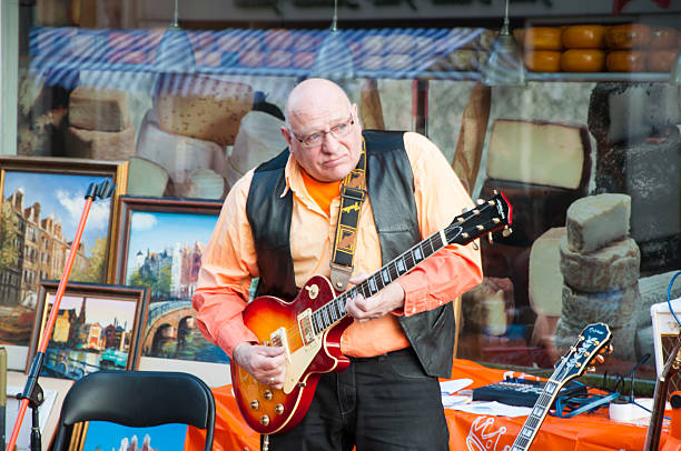Street musician plays the guitar during King's Day. Amsterdam. Amsterdam, the Netherlands - April 27, 2015: Street musician plays the guitar during the King's Day. prince musician stock pictures, royalty-free photos & images
