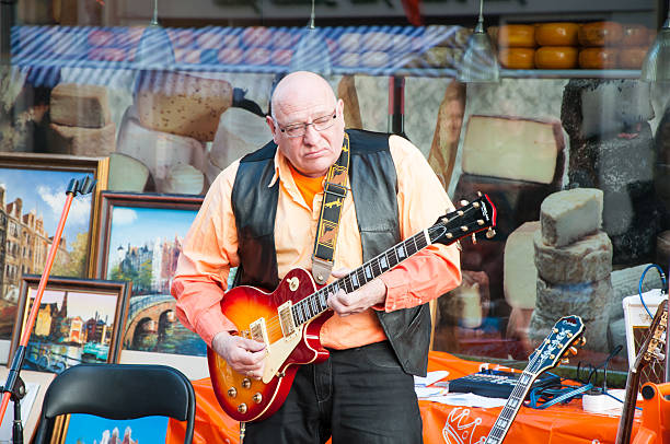 Street musician plays the guitar on King's Day. Amsterdam. Amsterdam, the Netherlands - April 27, 2015: Street musician plays the guitar on King's Day.  prince musician stock pictures, royalty-free photos & images