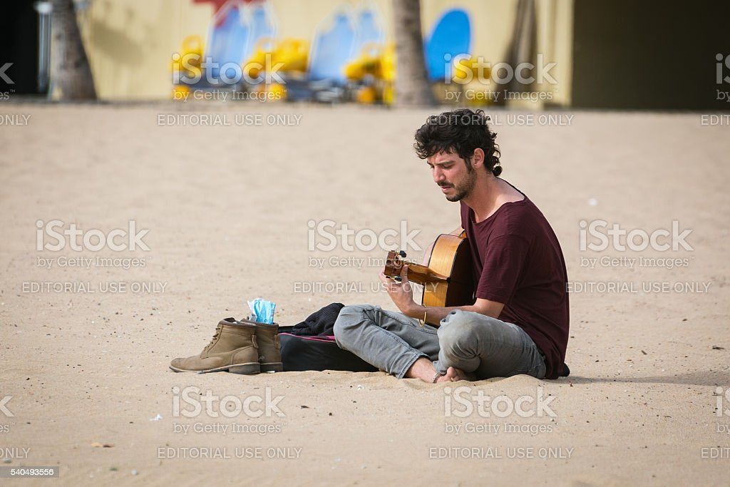 Street musician with a guitar sitting at sandy beach stock photo