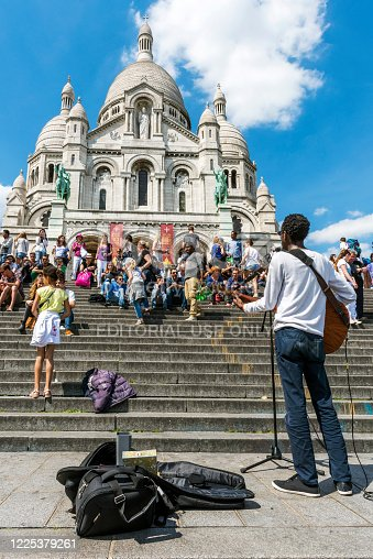 Paris, France - Jul 06, 2016: Tourists listening to the street musician playing the guitar on the stairs in front of the Sacre-Coeur Basilica in Paris, France.
