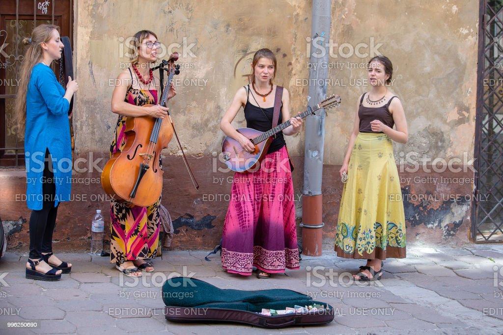 Street musicians entertain tourists on a sidewalkon in city center Lviv, Ukraine стоковое фото
