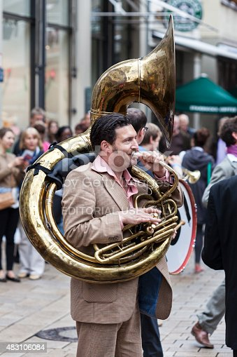 Wiesbaden, Germany - June 16, 2012: Street musician walking through the city center of Wiesbaden, Germany playing Jazz on a Sousaphone. Promotion for theatre festival