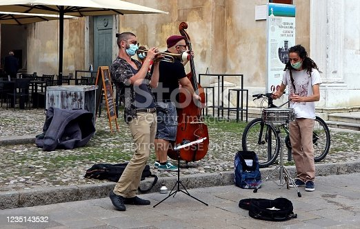 Udine, Italy. May 30, 2020. Street musicians play in the square with musical instruments and protective face masks, some days after the end of coronavirus lockdown