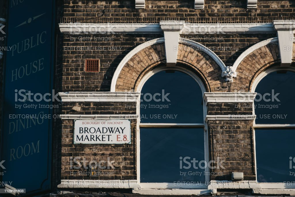 Street name sign on a building on Broadway Market, a shopping street...