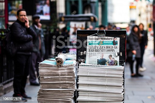 London, UK - 24 October, 2018: close up color image depicting a pile of free newspapers on the street in central London, UK. The headline of the newspaper is 'Fear takes hold as bad Brexit looms', making reference to the unstable political climate in the UK as it prepares to leave the European Union. People on the street are defocused in the background. Room for copy space.