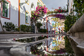 street of the port of Mogan that is reflected in a puddle of the street as if it were a mirror, white facades with green windows and abundant flowers