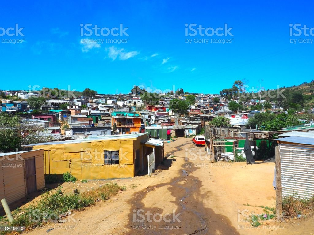 Street of colorful informal settlements, huts made of metal in the Township or Cape Flats of Stellenbosch, Cape Town, South Africa with blue sky and clouds background. stock photo