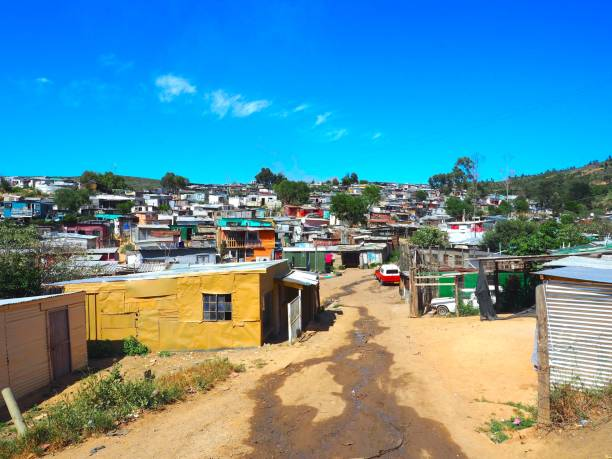 street of colorful informal settlements, huts made of metal in the township or cape flats of stellenbosch, cape town, south africa with blue sky and clouds background. - деревня стоковые фото и изображения