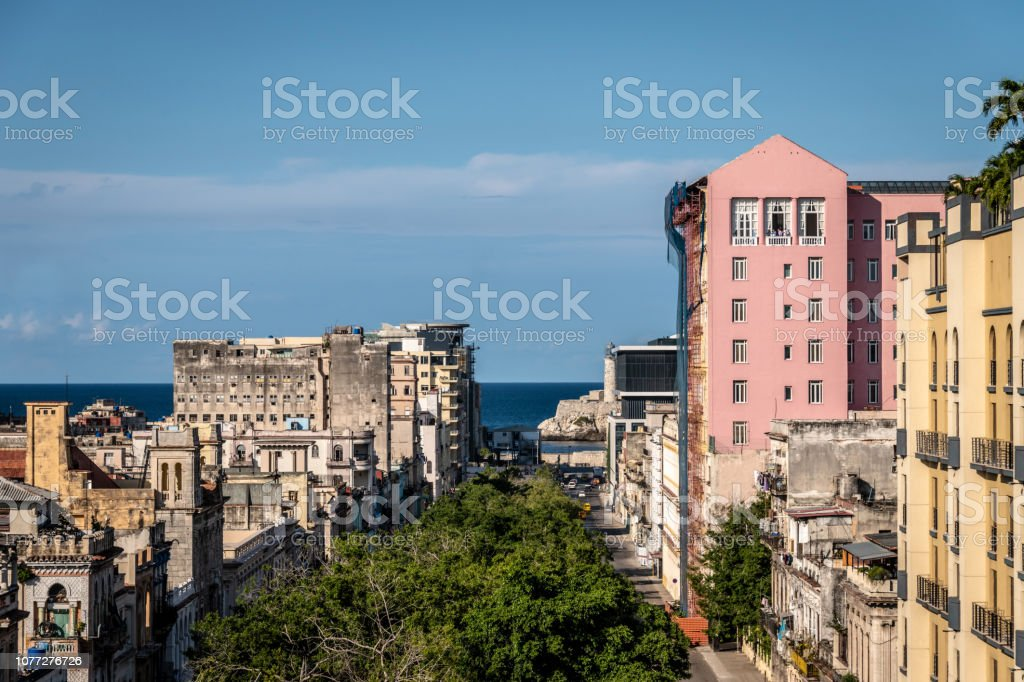 Street of dilapidated buildings leading to the sea in Havana stock photo