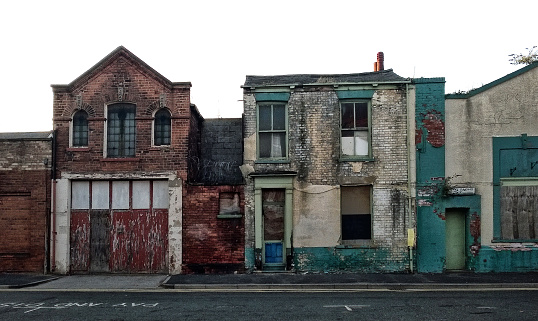 street of long abandoned and derelict collapsing houses and commercial buildings