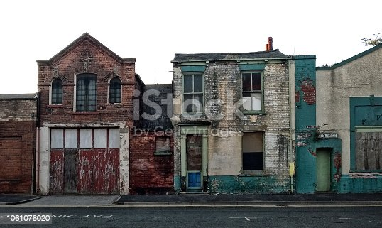 A street of long abandoned and derelict collapsing houses and commercial buildings