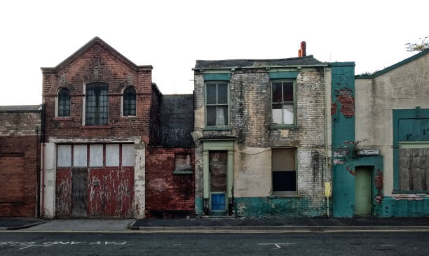 street of long abandoned and derelict collapsing houses and commercial buildings - dilapidated stock pictures, royalty-free photos & images