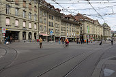 Bern, Switzerland - April 17, 2017: Buildings by a street in the old town and there are several people visible. On the roadway you can see the tram rails and the dense power grid is above. This is one of the countless wonderful places in Switzerland, which is a tourist attraction often visited by many tourists from all over the world.