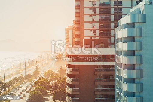 Street of Rio de Janeiro near beach and ocean in luxury Barra district with buildings and cars, on a hot sunny summer day, sunset or dawn, view from top, vintage colour filter