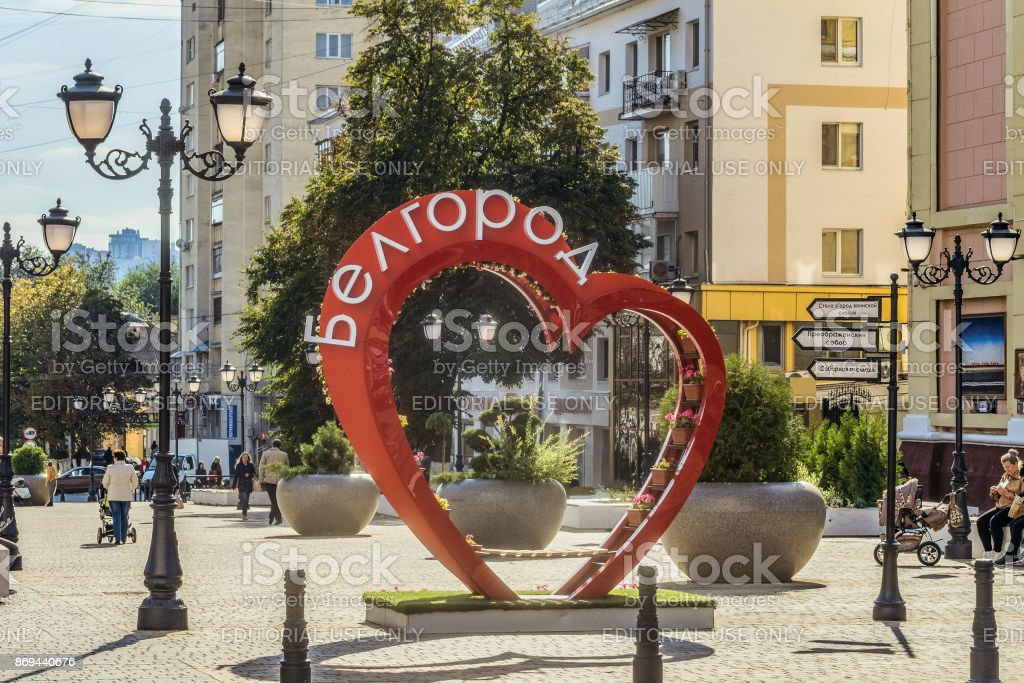 Street of the fiftieth anniversary of the Belgorod region. Pedestrian street in the old residential center of the city. Bench of love in the shape of a heart with flower pots. Belgorod, Russia. stock photo